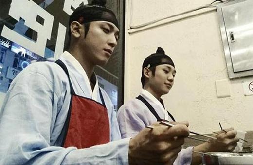 Yonghwa làm mặt nghiêm trọng trong bữa ăn với trang phục cổ trang cùng bạn diễn trong phim The Three Musketeer