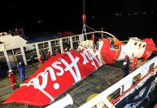 Phần đuôi của máy bay QZ8501 được đưa lên bờ. Tuy nhiên, kích thước quá khổ khiến nhà chức trách khó đưa chúng lên xe tải. Ảnh: Strait Times