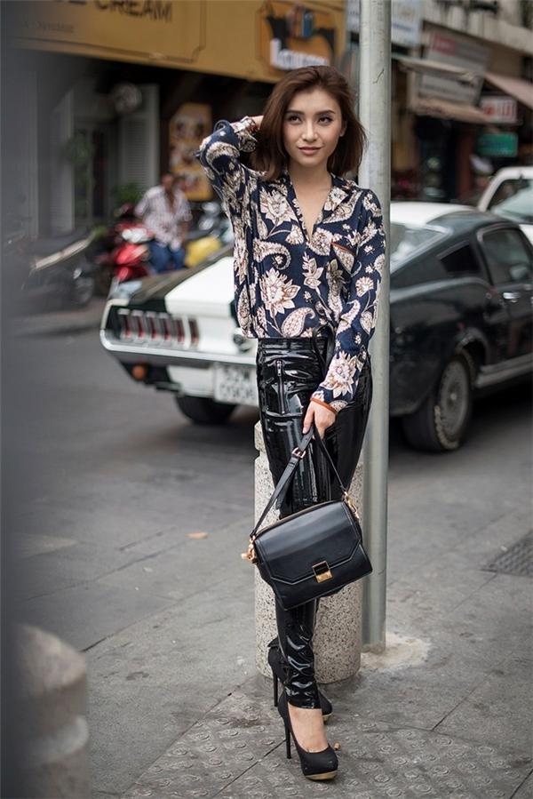 Vẫn là thiết kế legging da bóng nhưng nữ ca sĩ trẻ lại vô cùng khéo léo khi mix - match cùng áo sơ mi tay dài hoa tiết cầu kì. Điểm nhấn chính là túi xách, giày tông xuyệt tông.