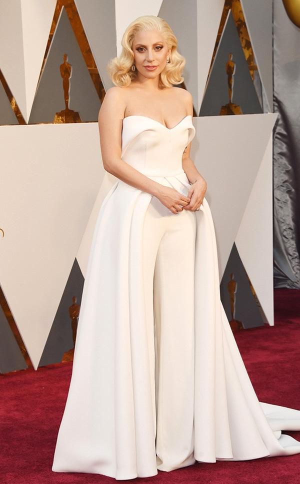 """Thời gian gần đây, Lady Gaga bắt đầu """"hiền"""" hơn trên thảm đỏ. Đến với Oscar lần thứ 88, nữ ca sĩ đình đám Hollywood chọn diện thiết kế có tông trắng tinh khôi, nhẹ nhàng của nhà mốt Bradon Maxwell. Thiết kế là sự kết hợp hài hòa, tinh tế giữa jumpsuit hiện đại cùng chân váy xếp li phồng xòe điệu đà, gợi cảm."""