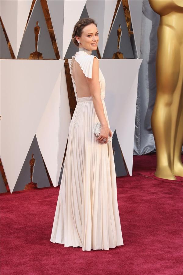 Chiếc váy trắng xếp li của nhà mốt Valentino vừa mang đến vẻ ngoài ngọt ngào, điệu đà nhưng không kém phần gợi cảm bởi những đường cắt táo bạo cho Olivia Wilde.