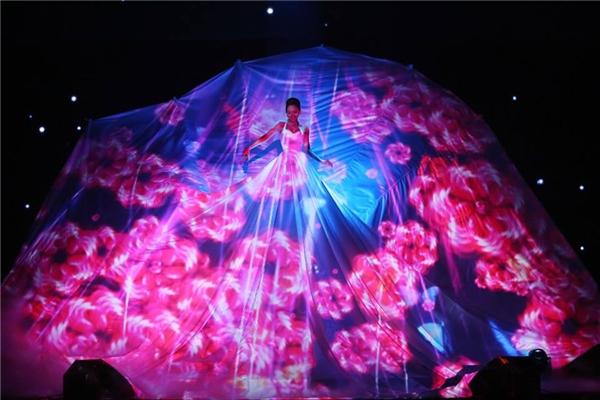 Giang Hồng Ngọc, Tóc Tiên cùng gây ấn tượng với những chiếc váy khổng lồ. Nền vải được sử dụng làm màn chiếu nhằmphô diễn những họa tiết bằng ánh sáng.