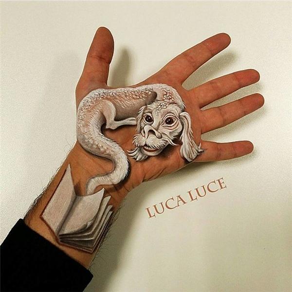 """Chú rồng và quyển sách như sắp """"rơi"""" khỏi bàn tay.(Ảnh: Luca Luce)"""