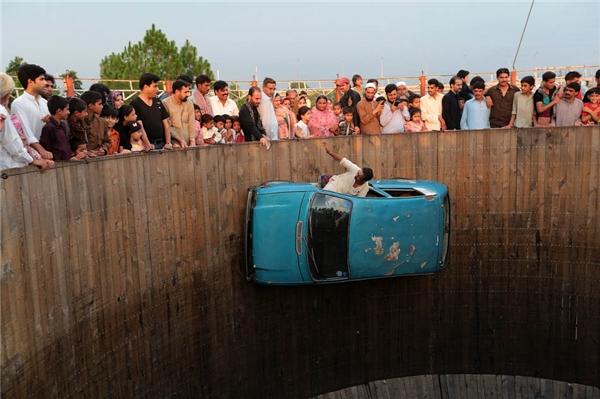 Feiyanzoubi người Pakistan đang thể hiện một màn biểu diễn nguy hiểm đầy ngoạn mục. Anh lái xe chạy quanh một cái hố cao và nhoài người ra chào khán giả.