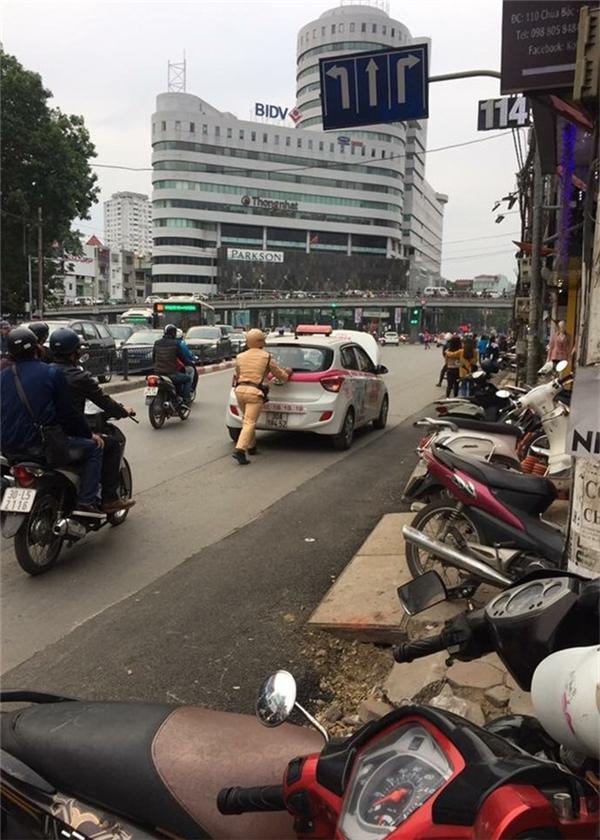 Chiến sĩ CSGT giúp đỡ tài xế taxi đẩy chiếcxe bịchết máy. (Ảnh: Internet)