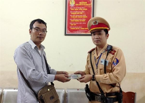 Thượng úy Nguyễn Đức Thắngtrả lại giấy tờ và tiền bị đánh rơi cho chủ nhân của nó. (Ảnh: Internet)