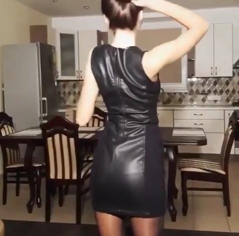 Cô gái diện váy đen ôm sát, quay lưng về phía camera và búi tóc cao.