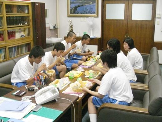 Các bạn trong lớp ngồi quây quần với cô giáo chủ nhiệm, vừa ăn vừa trò chuyện.